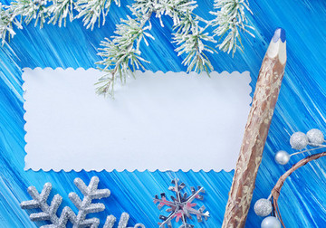 White card on a wooden, blue background. Fir bough upper edge of the frame, silver stars and bough with frosted berries at the lower edge. On the right of the card is a wooden pencil with a blue tip.